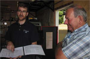 Terrance Sauve and Charlie Forman discuss the performance of a Froling Hydronic heater during a recent OSCIA stop at Forman Farms.