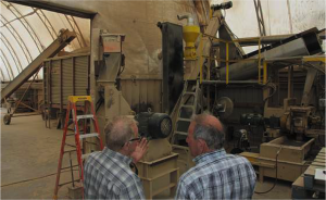 OSCIA Executive Officer, Research and Business Development, Harold Rudy and Forman Farms' Charlie Forman discuss the farm's experimental pellet mill.