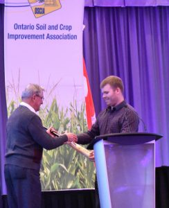 2017 Soil Champion Eric Kaiser (left) congratulated by 2016 Soil Champion Tyler Vollmershausen (right) at OSCIA Annual Conference