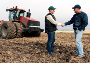 Two farmers in a field shaking hands in front of a tractor