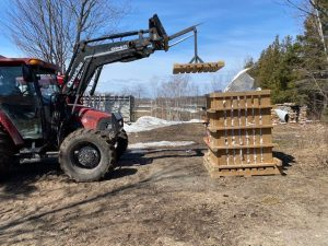 Tractor placing lid on pallet system